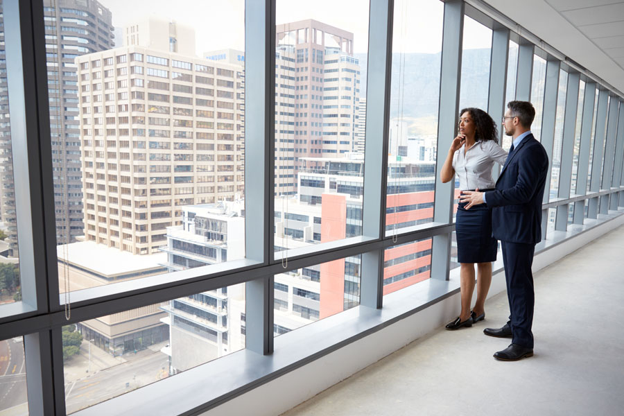 Business Insurance - Real Estate Investors Looking Out the Window Pondering the Next Deal